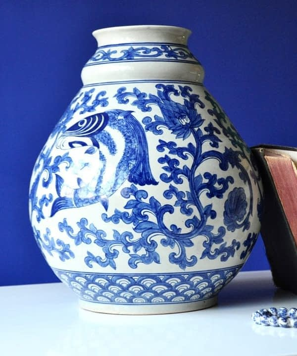 A large, typically Thai blue and white pot with swimming fish and lotus flower motifs.