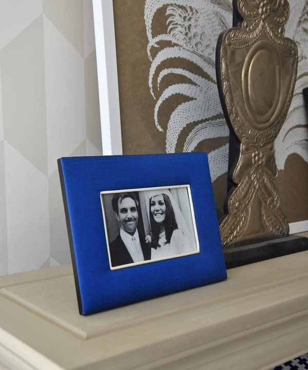 A Thai -silk, Royal blue, photograph frame with a family wedding picture on a neutral-hued bookshelf.