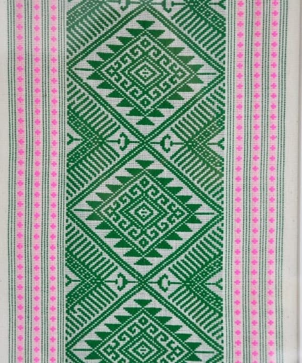 Detail of a framed textile wall art piece in pea green with candy pink accents. The textile was hand-loomed in northern Thailand.