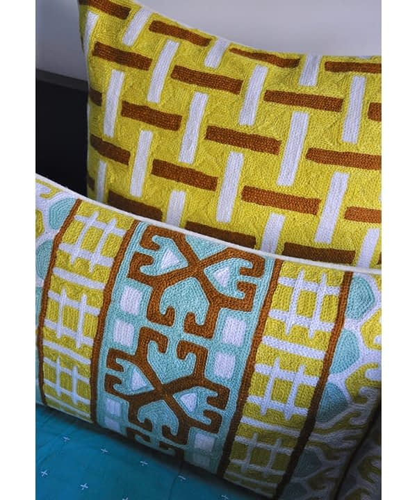 Detail of the Kashmiri crewelwork cushions in turquoise and chocolate with yellow geometric background from Telescope Style.