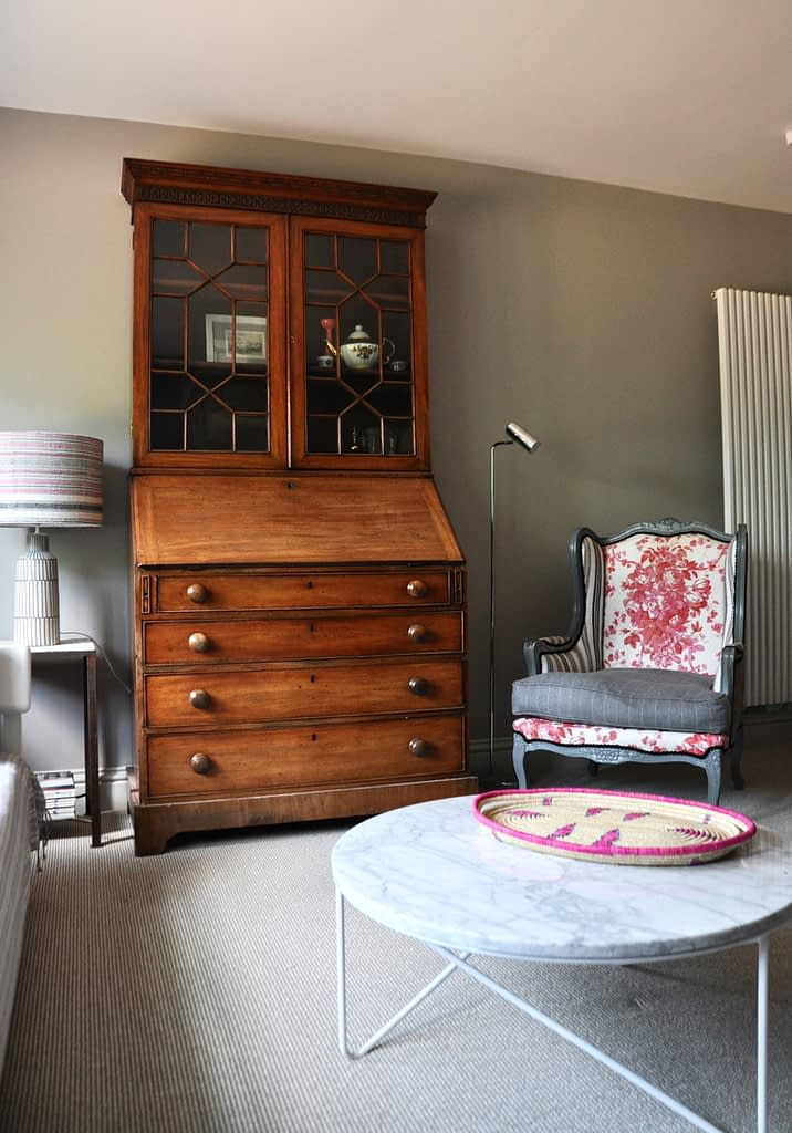 Lockdown decorating might involve shifting furniture around and experimenting. This room displays an eclectic mix of mahogany dresser, floral upholstered bergère chair and modern marble coffee table.