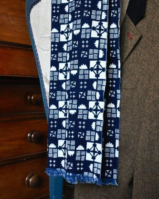Shot of a geometric indigo print cotton scarf hung on a tweed jacket with a mahogany chest in the background.