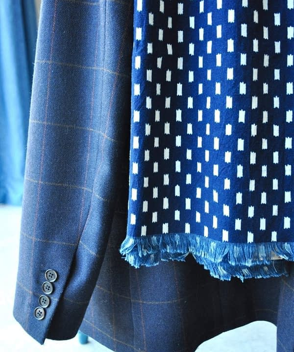 Detail of an indigo blue scarf hung on a tweed check jacket.