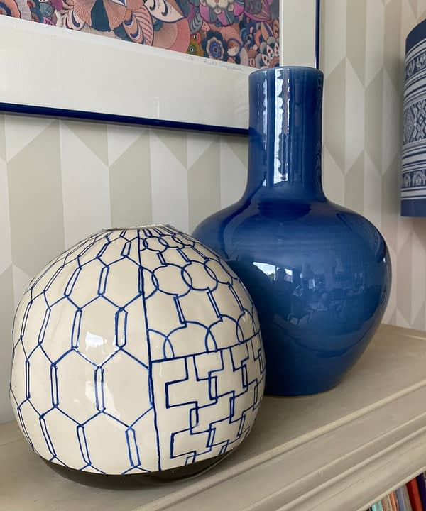 Two blue, Asian-style, ceramic pots on a bookshelf with subtle geometric wallpaper in the background.