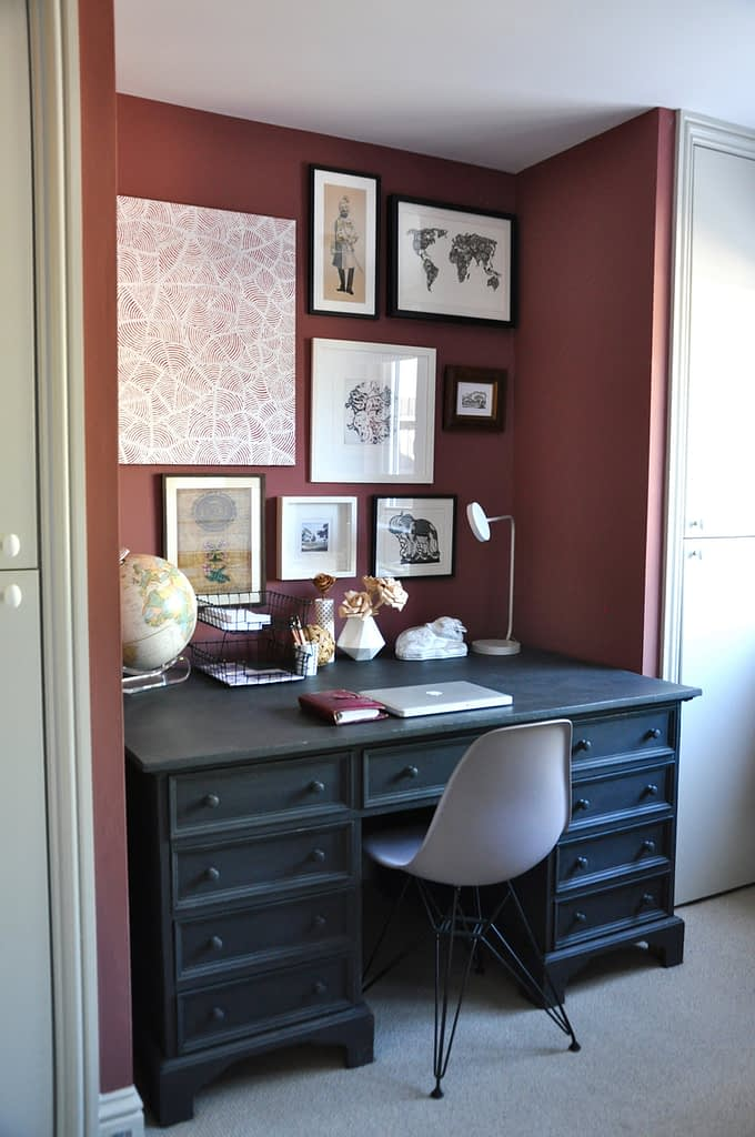 A classically-styled home office with a charcoal 'partner' desk and eclectic artwork.