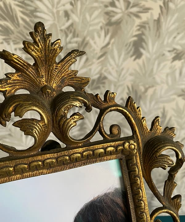 Detail of the patinated brass finish on a vintage photo frame sourced in Spain.
