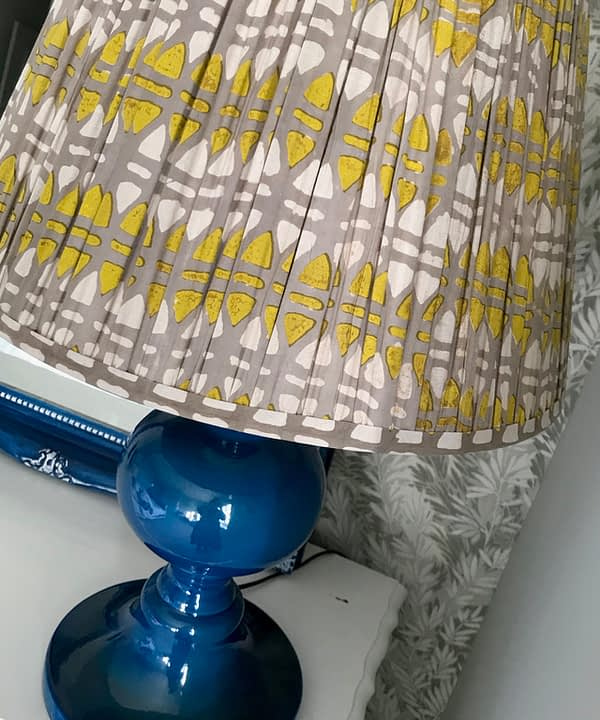 Lampshades in chartreuse and putty, block-printed in India on cotton voile, displayed here on a blue ceramic lamp base.