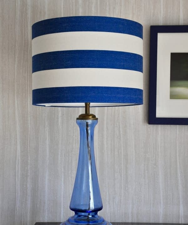 A Royal blue striped lampshade on a blue glass lamp base against a pale backdrop.