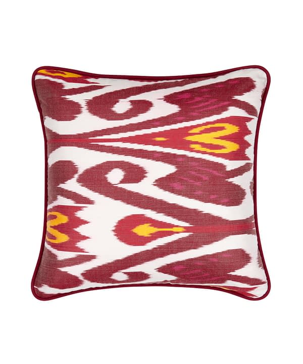 Red and white cushions with a yellow accent in a striking, luxury, silk Ikat.