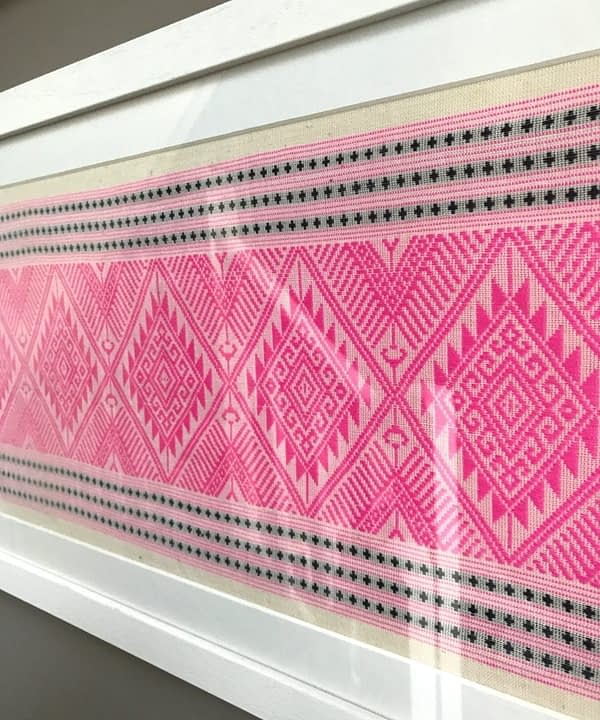 A framed candy pink and navy woven Thai textile.