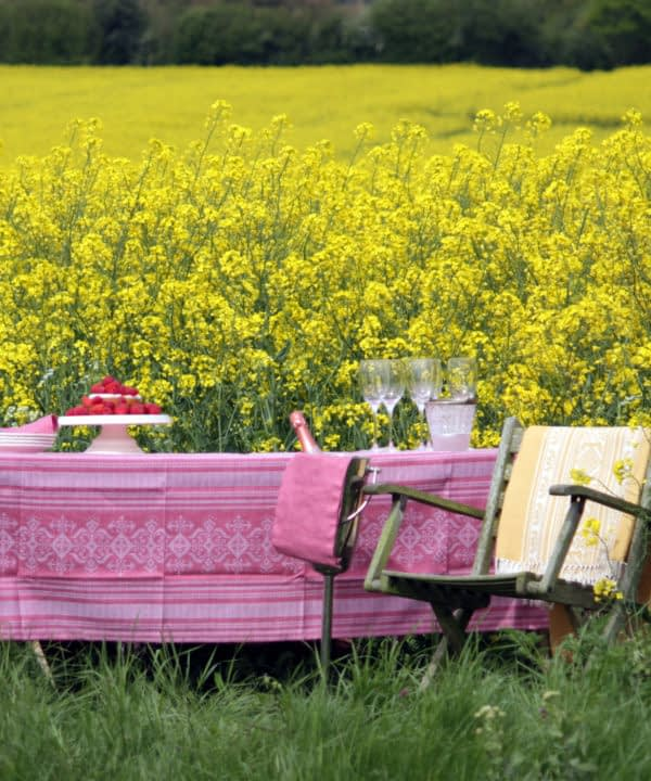 Pink linen tablecloth with subtle motifs that reference Hungarian folk patterns. Draped over a table in a field of yellow flowers.