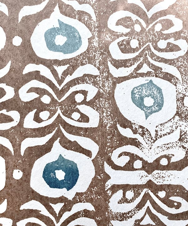 Detail shot of a brown and blue wallpaper with a Middle-Eastern inspired design.