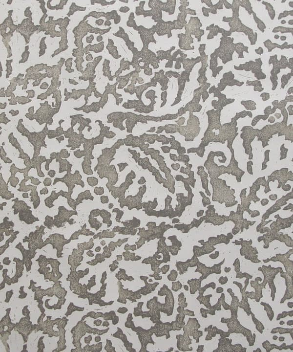 A close up of the Majolica, Italian inspired grey patterned wallpaper in a warm grey with a pale off-white ground.