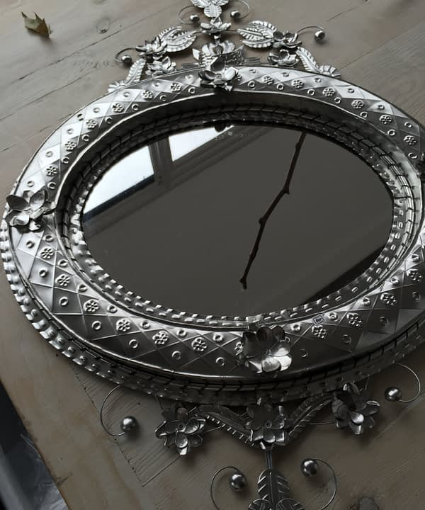 Tin art mirror from Mexico in landscape orientation laid on a wooden table with twig reflections.