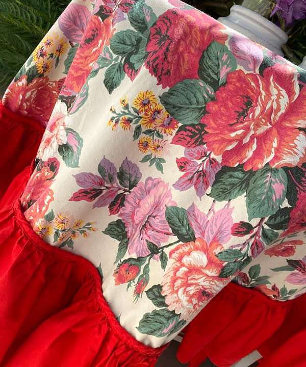 A vintage floral tablecloth with a bold, red frill.