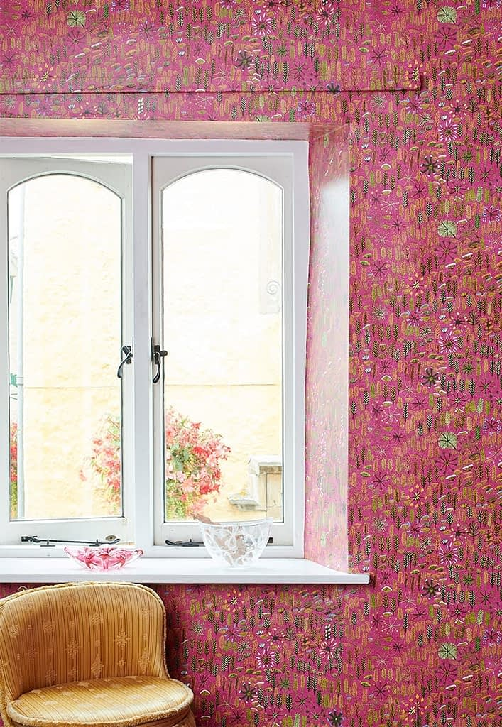 Aboriginal culture wallpaper 'Betty' in pink shown in a room setting by a window with chair in foreground.