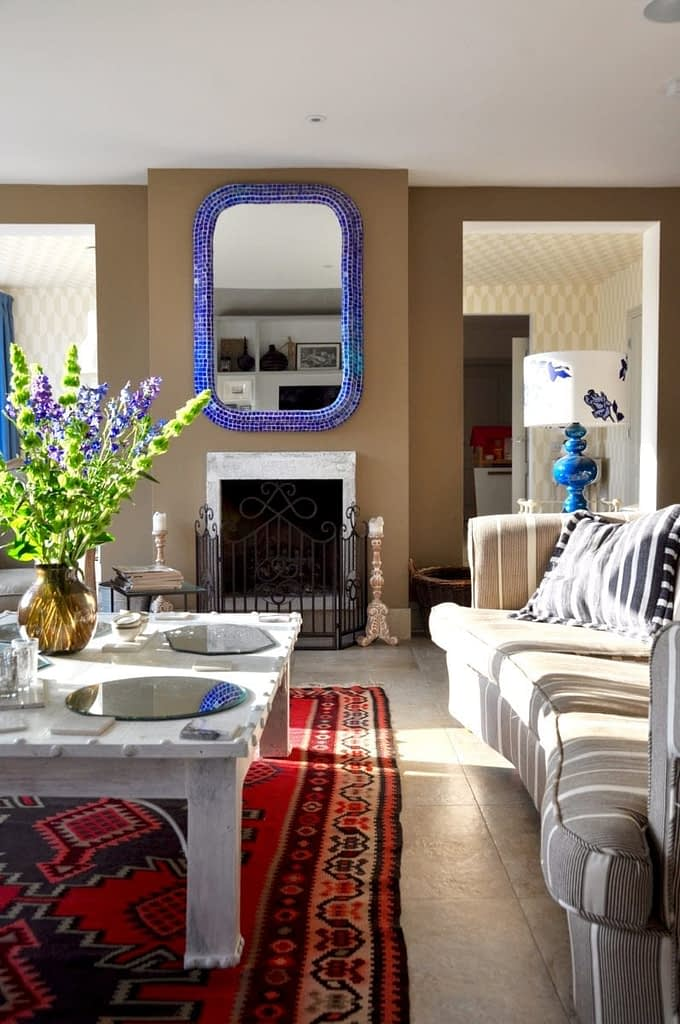 A sunny relaxed, eclectic sitting room wit a Turkish rug, stripy sofa, blue mosaic-tiled mirror and white-washed Indian coffee table.