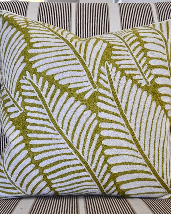A chartreuse green, crewel-work cushion, handmade in Kashmir available from Telescope Style.