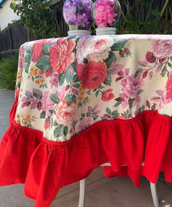 Floral tablecloth with a bold, red frill.