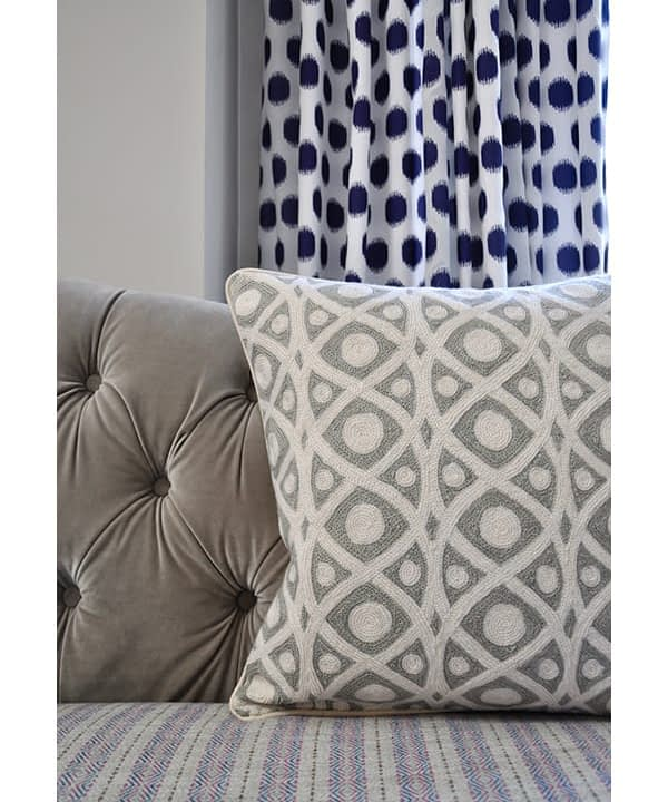 Cream and grey crewelwork cushions from Kashmir on a grey, buttoned, velvet sofa with a spotted blue curtain behind.