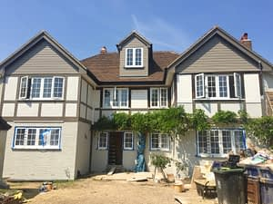 A 1930s exterior house renovation mid-project, featuring gable ends, mock-Tudor beams, painted beams and brickwork.