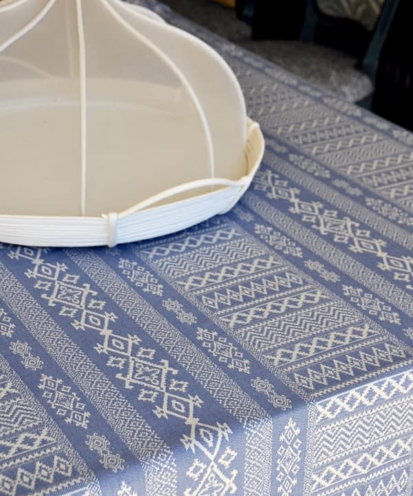Detail of a luxury, blue linen tablecloth with Arabian architectural motifs pattern with an elegant white Thai style food cover.