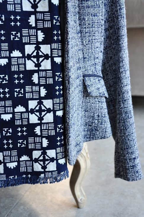 Close-up of a geometric print cotton scarf hung on a ladies blue tweed jacket on a chair.