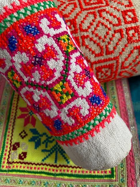 Close up shot of colourful, vintage Thai embroidered trims used for framed wall art.