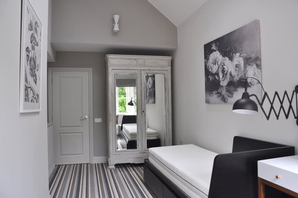 A grey room scheme featuring a French painted armoire, a day bed, a peony print and stripy, neutral carpet.