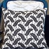 A chic black and white botanical cushion in African Dutch wax print fabric on a blue French chair.