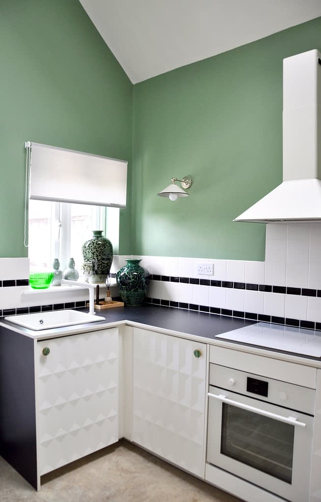 A modern, white, compact kitchen with black worktop, sage-green walls and monochrome, tiled splashback.