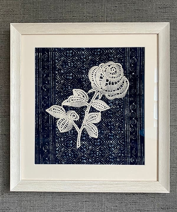 Textile art lace rose displayed against hand-dyed Thai indigo cloth.