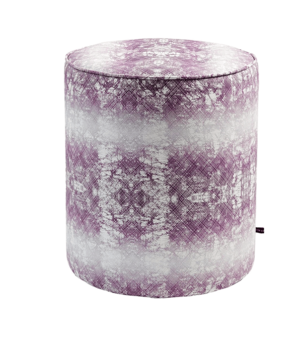 A purple pouffe with an African-inspired design with faded horizontal stripes.