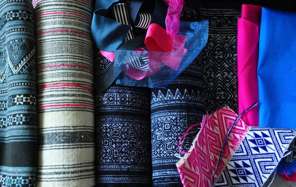 A collection of pink and indigo Thai textiles and ribbons.