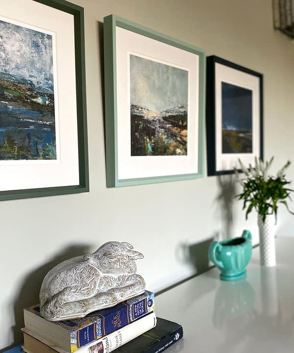 Northern Ireland prints hung in a row and framed in toning shades of green and blue above a sideboard.