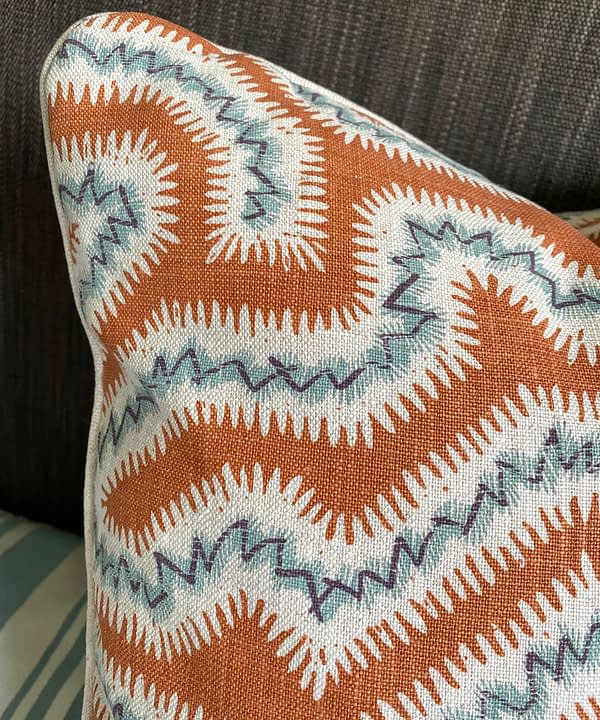 Detail of a burnt orange cushion with blue accents hand-printed on linen.