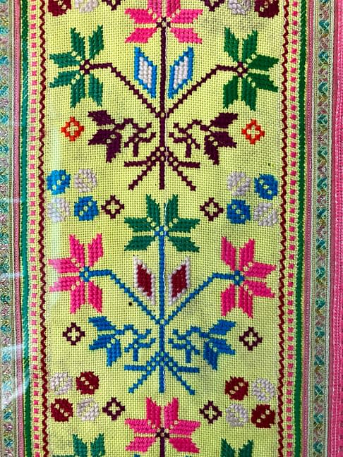 Close up detail of a framed Thai textile in yellow, pink, blue and green.
