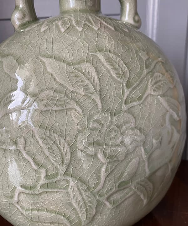 Close up detail of a hand-decorated celadon pottery pot.