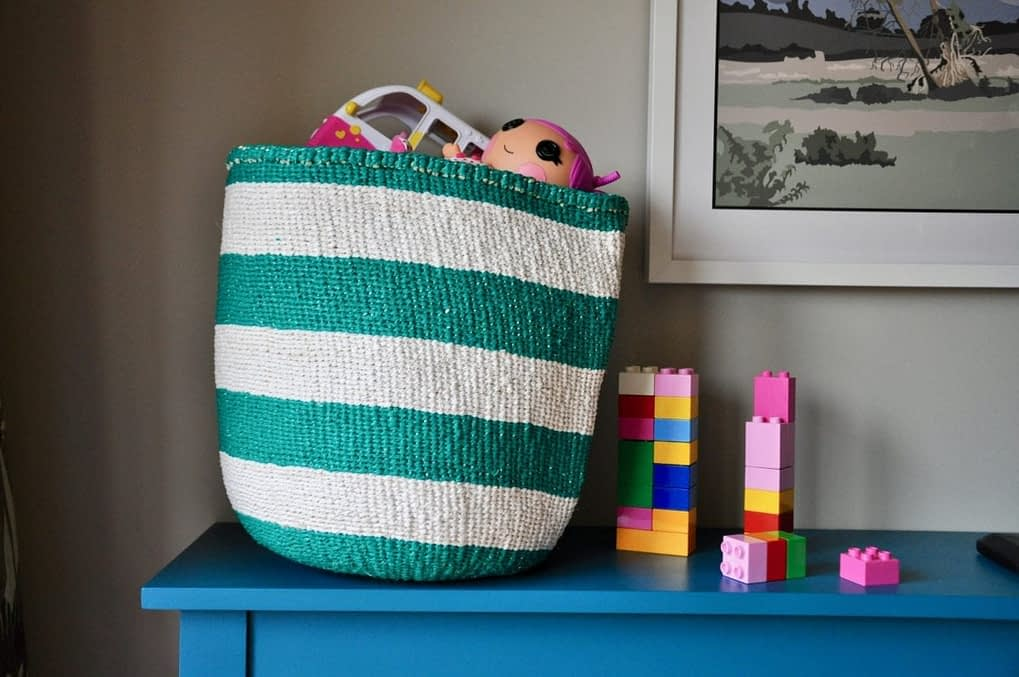 A landscape shot of a stripy jade woven basket with colourful kids toys inside on a teal sideboard.