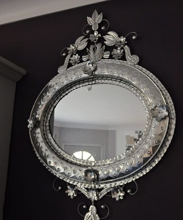 A unique, oval, hand-stamped tin, decorative, Mexican mirror hung against a dark painted wall.