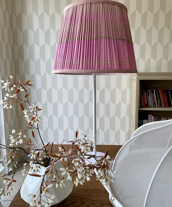 Pale pink lampshades in gathered cotton. The lampshade shown here is styled with a simple white metal base with white blossom in a vase in the foreground and neutral geometric wallpaper behind.