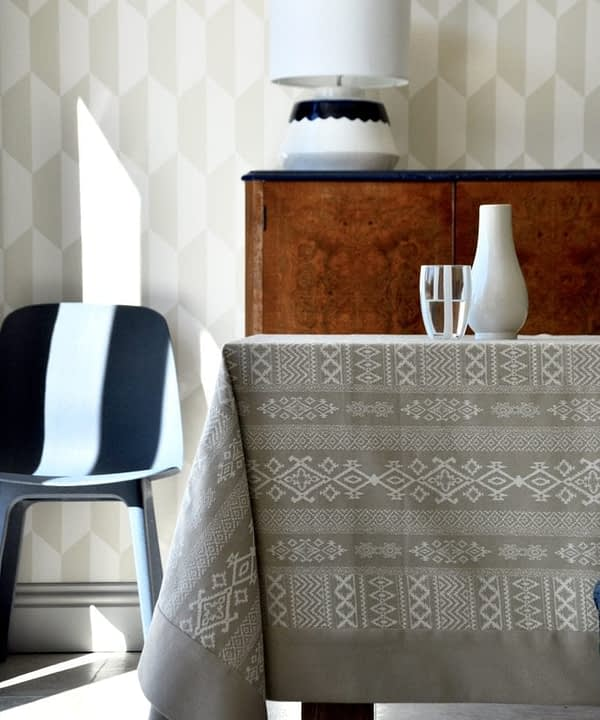 A neutral tablecloth with subtle architectural detailing is styled up in a modern dining room setting with blue chair, brown wood drinks cabinet and geometric wallpaper in the background.