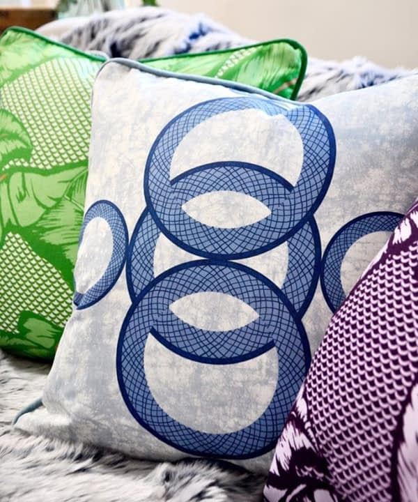 Boldly patterned African style cushions on a sofa.