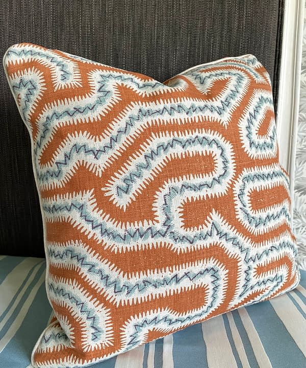 A hand print fabric burnt orange cushion with soft blue accents in a Moorish-inspired, maze-like design on linen.