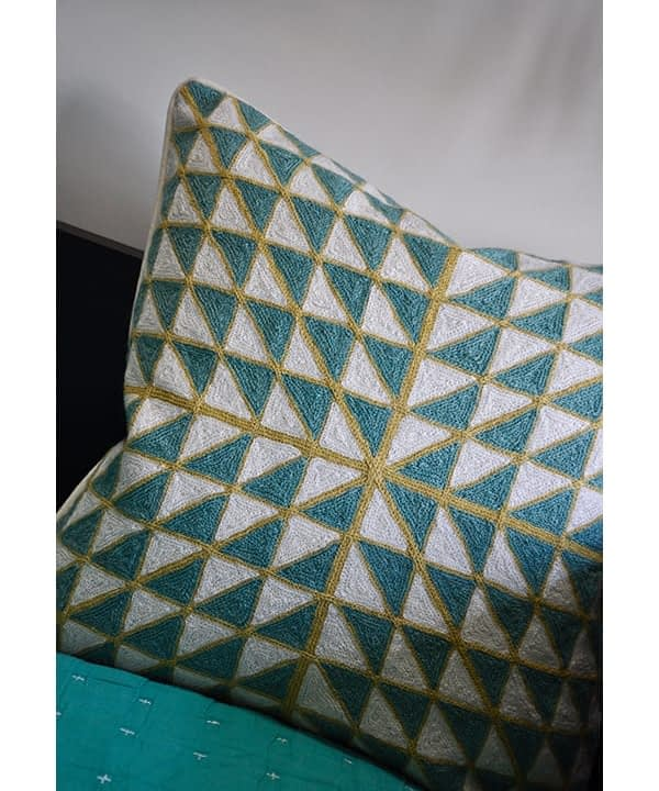 Teal crewelwork cushions with lime and geometric pattern.