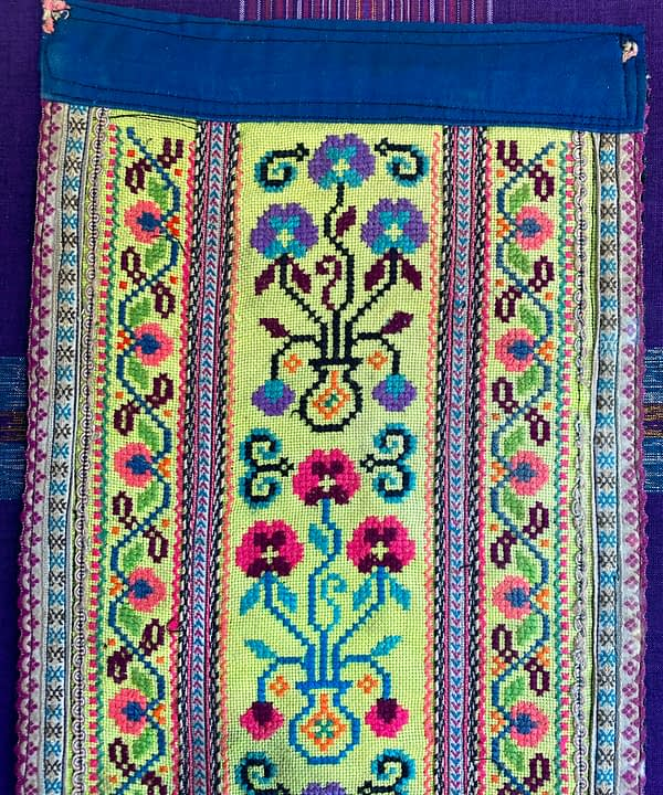 Fabric wall art showing a section of an embroidered Thai costume panel.