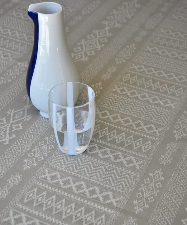 Detail shot of the neutral tablecloth woven with elegant architectural details and shown on a dining table with a white-striped water glass and modern ceramic jug.