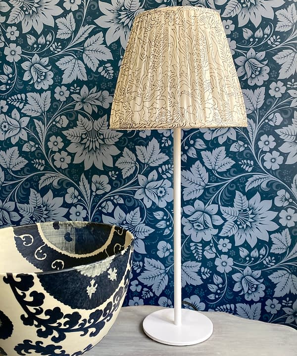 A vintage silk lampshade on a white candlestick base on a table with black and white bowl and floral folk wallpaper in dark blue behind.
