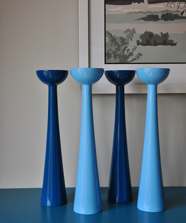 Coloured candlesticks in glossy blue hues sat on a teal painted sideboard.
