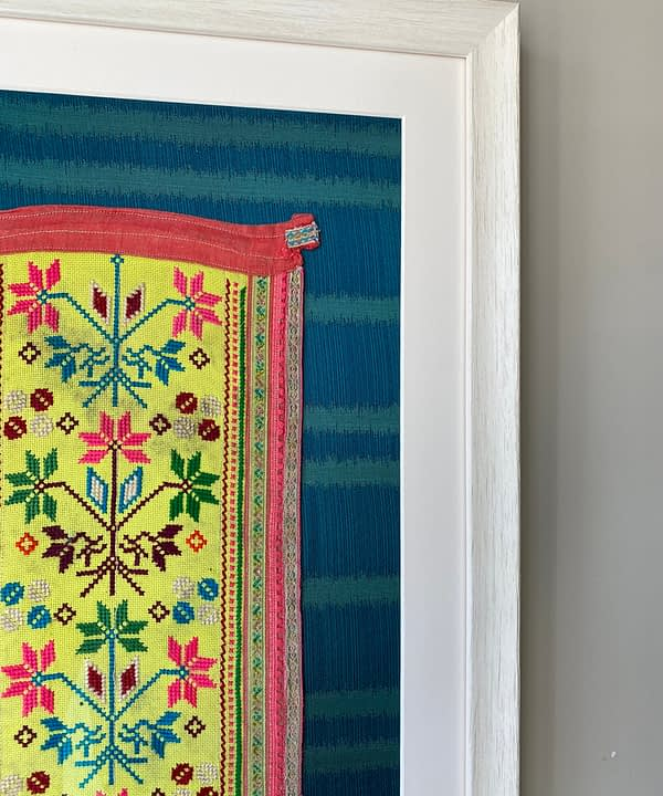 Section of a Thai embroidered panel framed and ready for hanging.